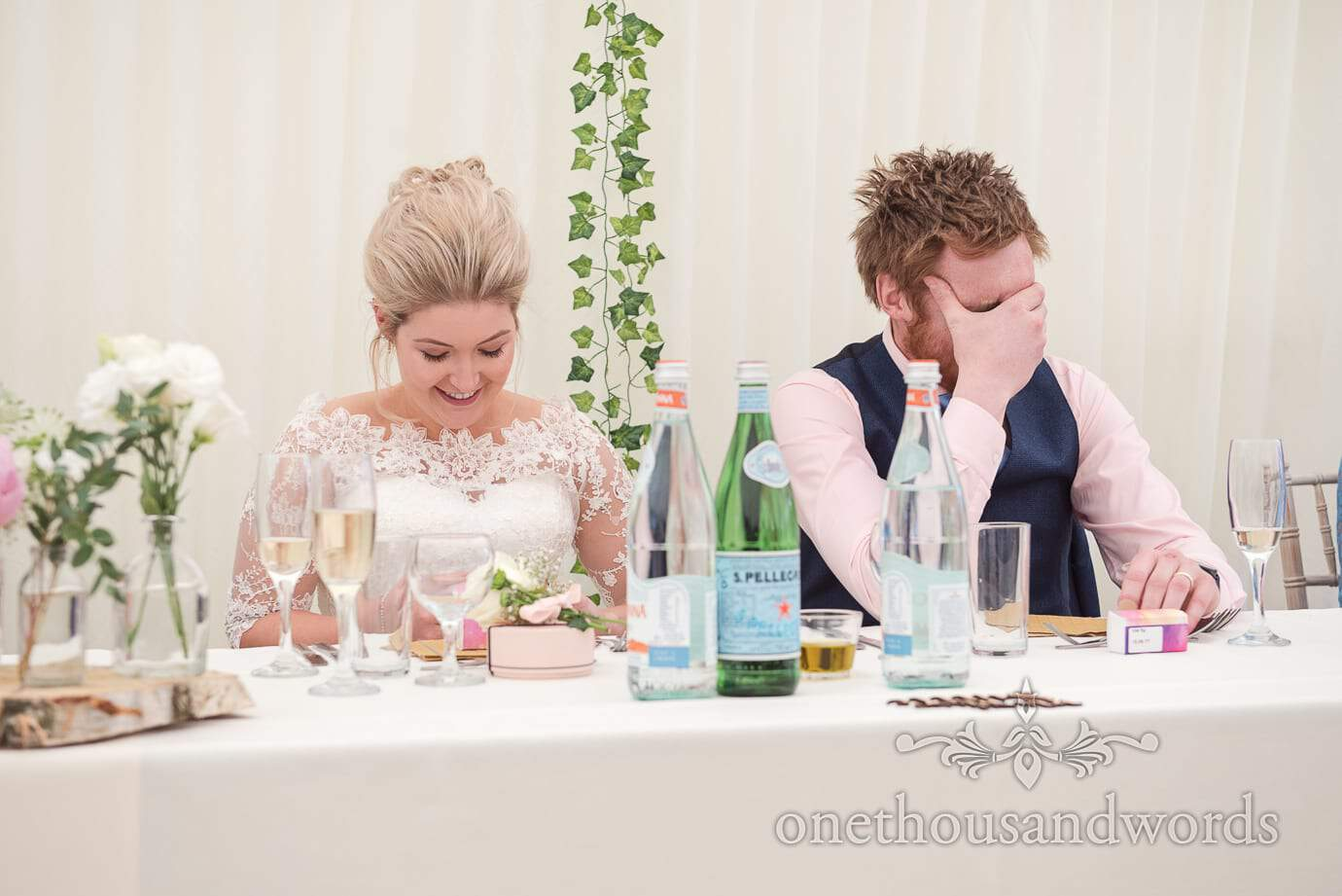Groom holds head in hands during country wedding speeches in marquee with ivy