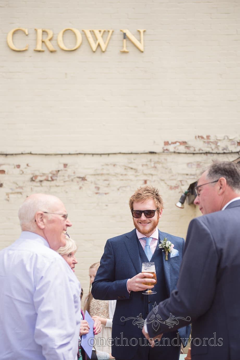 Groom in Blue suit drinks a beer on wedding morning at Crown Pub