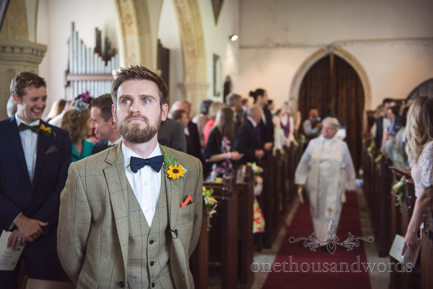 Groom in brown tweed and bow tie waits in church for arrival of his bride