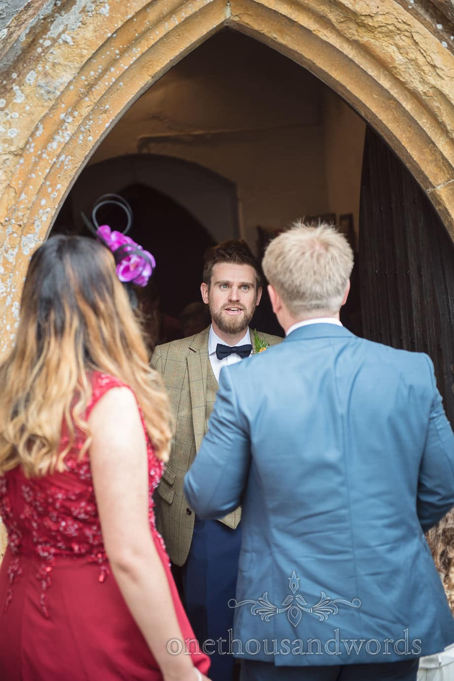 Groom in brown tweed greets wedding guests under stone church entrance archway
