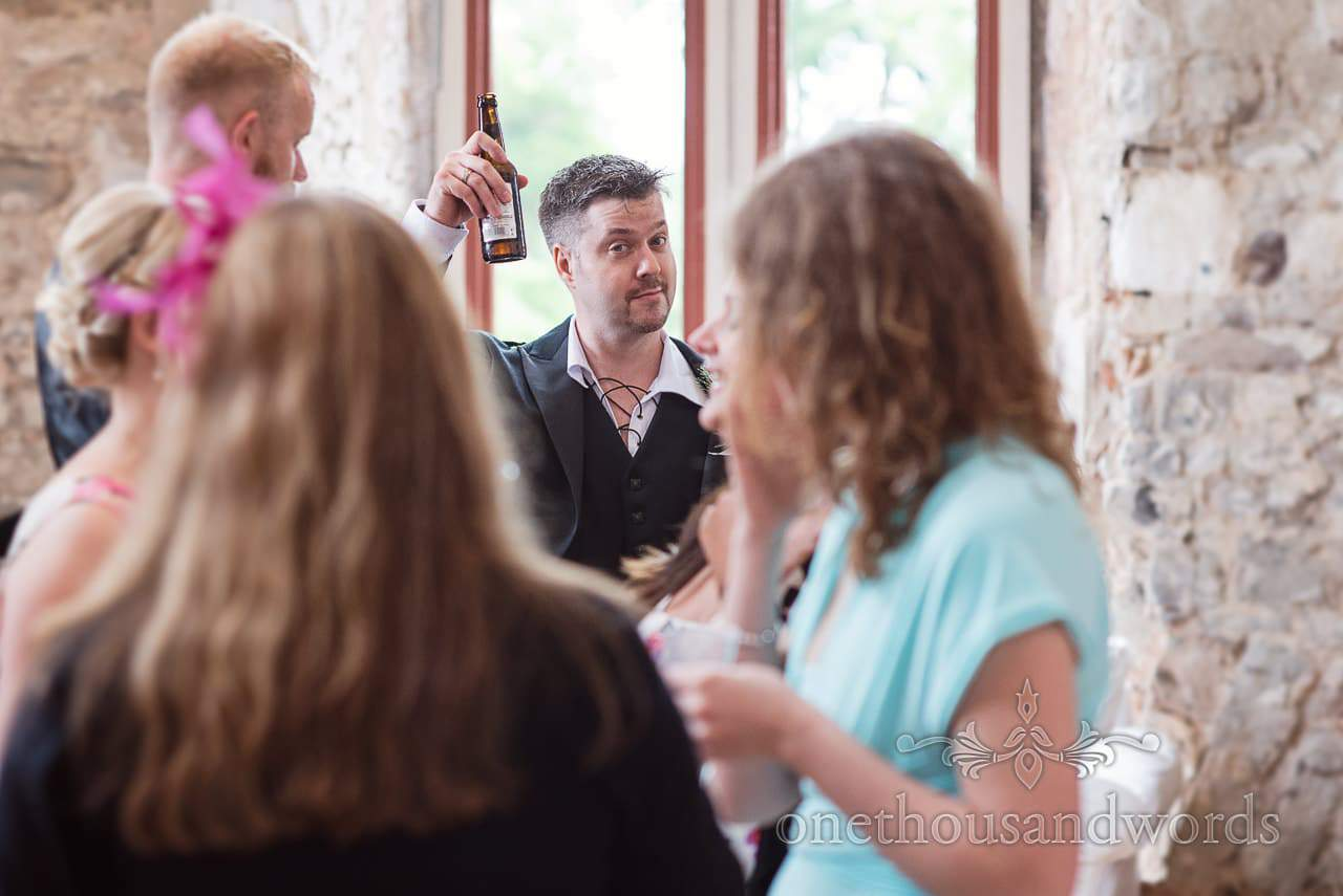 Groom in Jacobian shirt raises a bottle of beer at Lulworth Castle wedding in Dorset