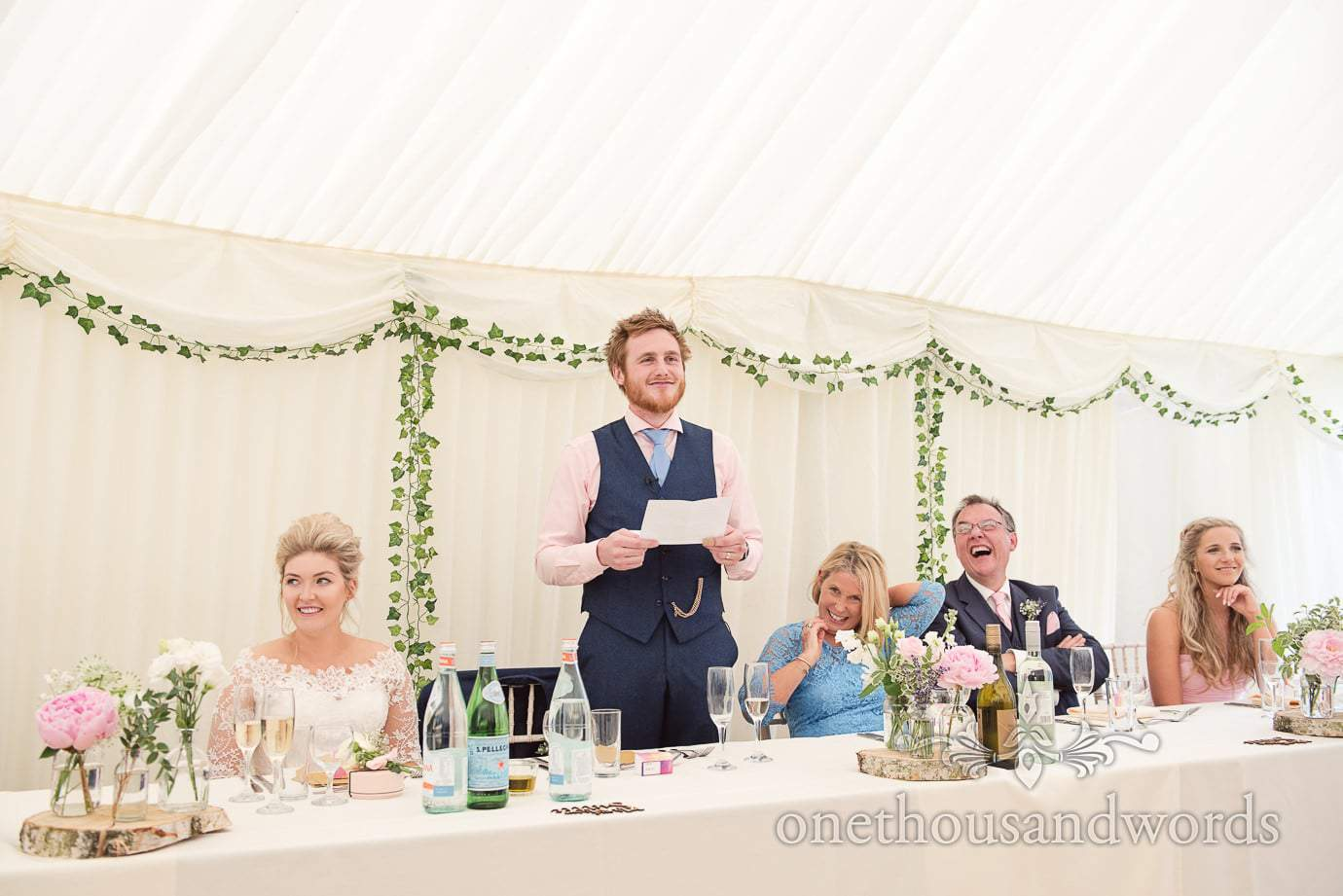 Groom in pink shirt and blue quit makes wedding speech in country wedding marquee