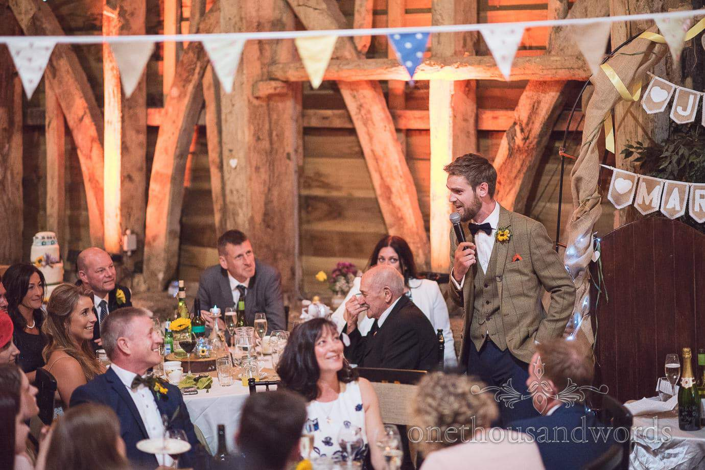 Groom in tan tweed suit delivers speech at rustic wedding in wooden barn with bunting