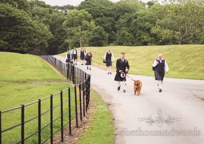 Groom leads his party up the driveway at Lulworth castle wedding