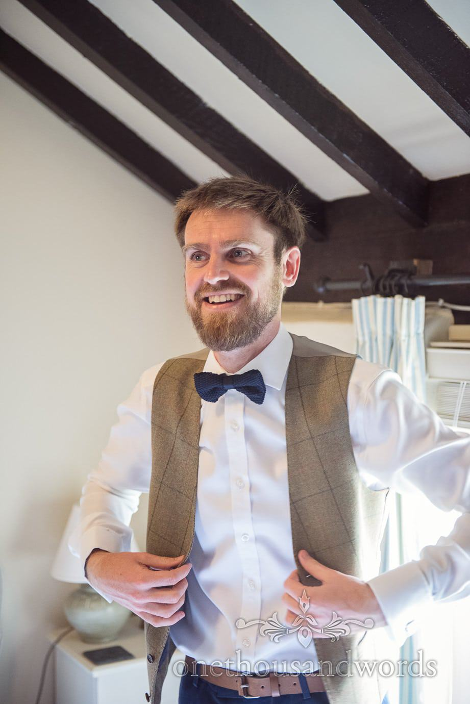 Groom prepares for rustic wedding day with blue bow tie and brown tweed waistcoat