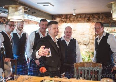 Groom raises his glass with groomsmen on morning of Lulworth castle wedding