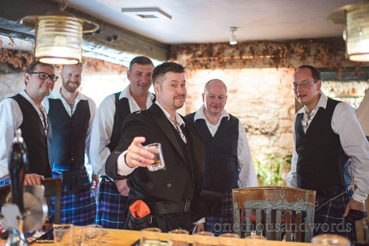 Groom raises his glass with groomsmen on morning of Lulworth castle wedding