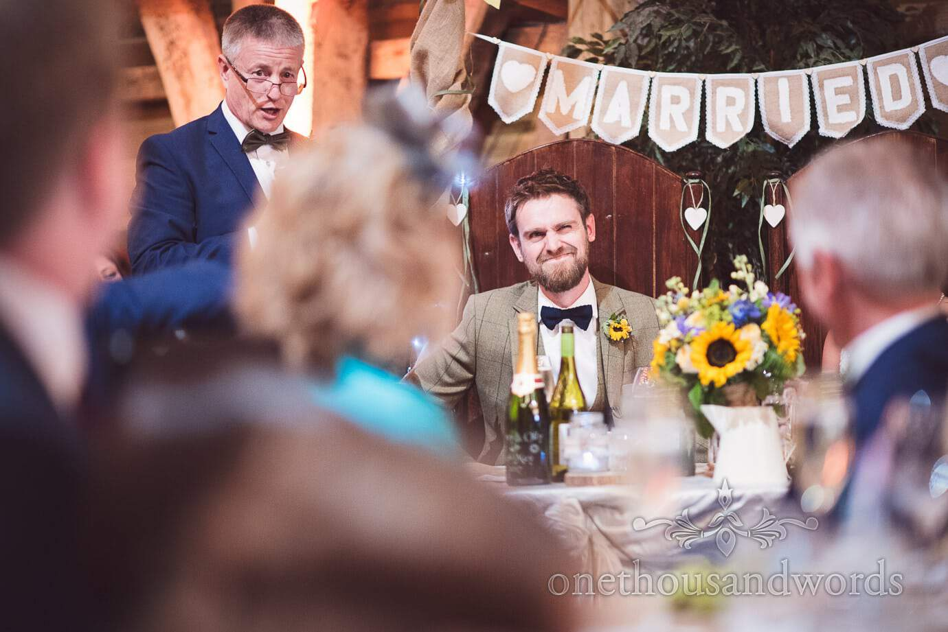 Groom reaction to father of the bride speech at rustic barn wedding