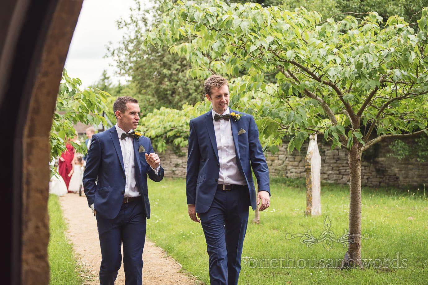Grooms men in blue suits and bow ties walk to countryside church wedding ceremony