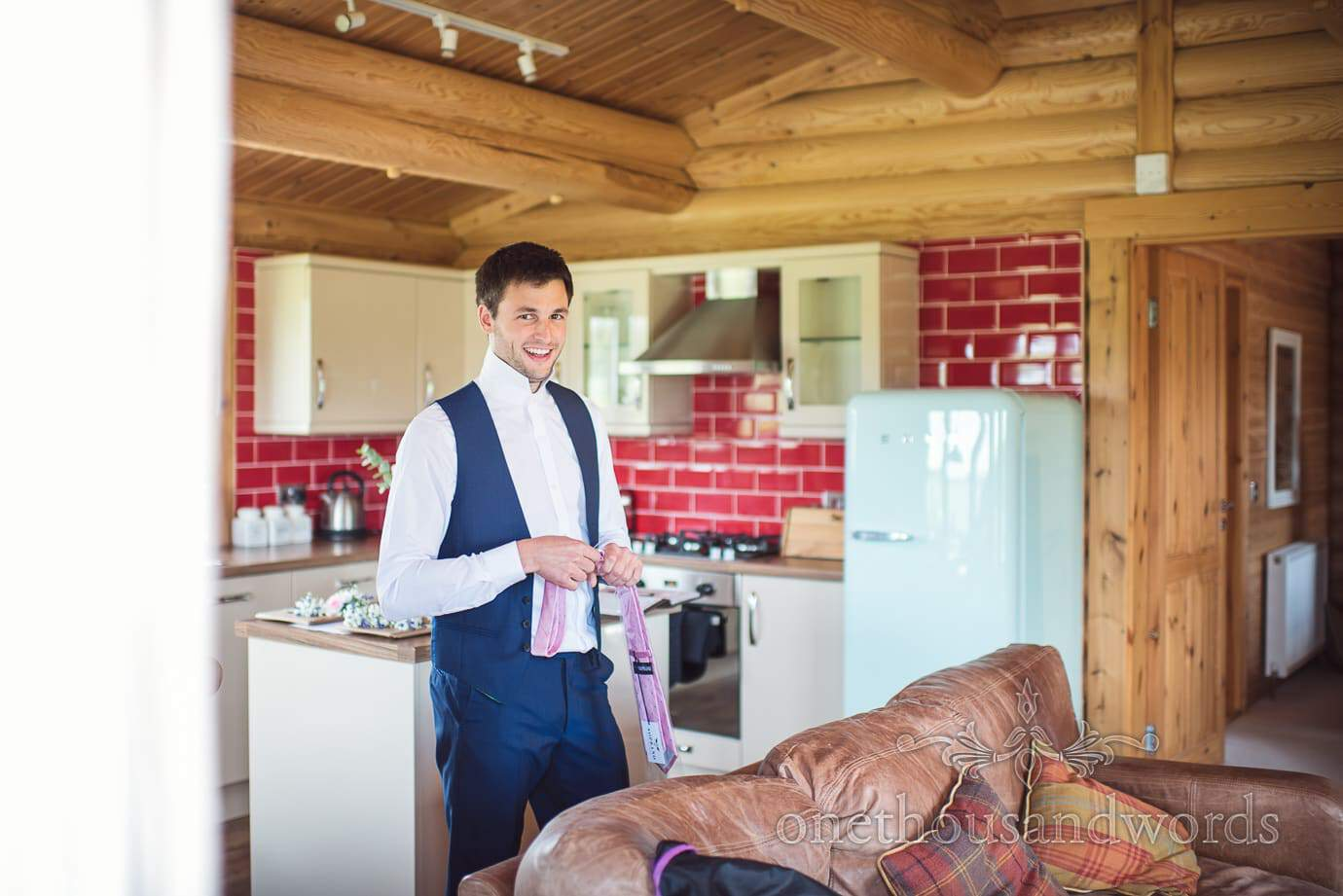 Groomsman in blue suit with pink tie prepares in wood and red tile lodge