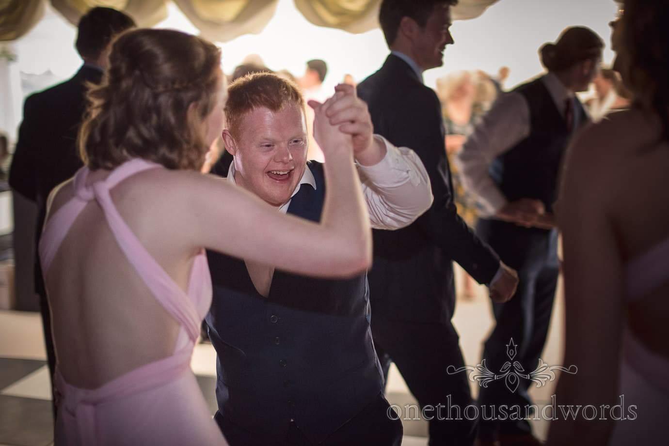 Groomsman in blue waistcoat dances with bridesmaid on wedding marquee dance floor