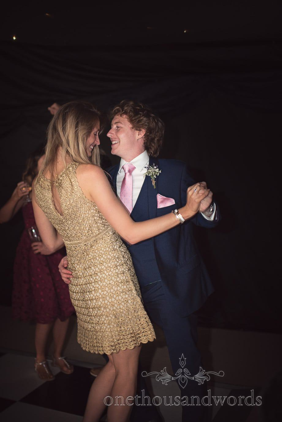 Groomsman in blue wedding suit dances with partner on black marquee dance floor