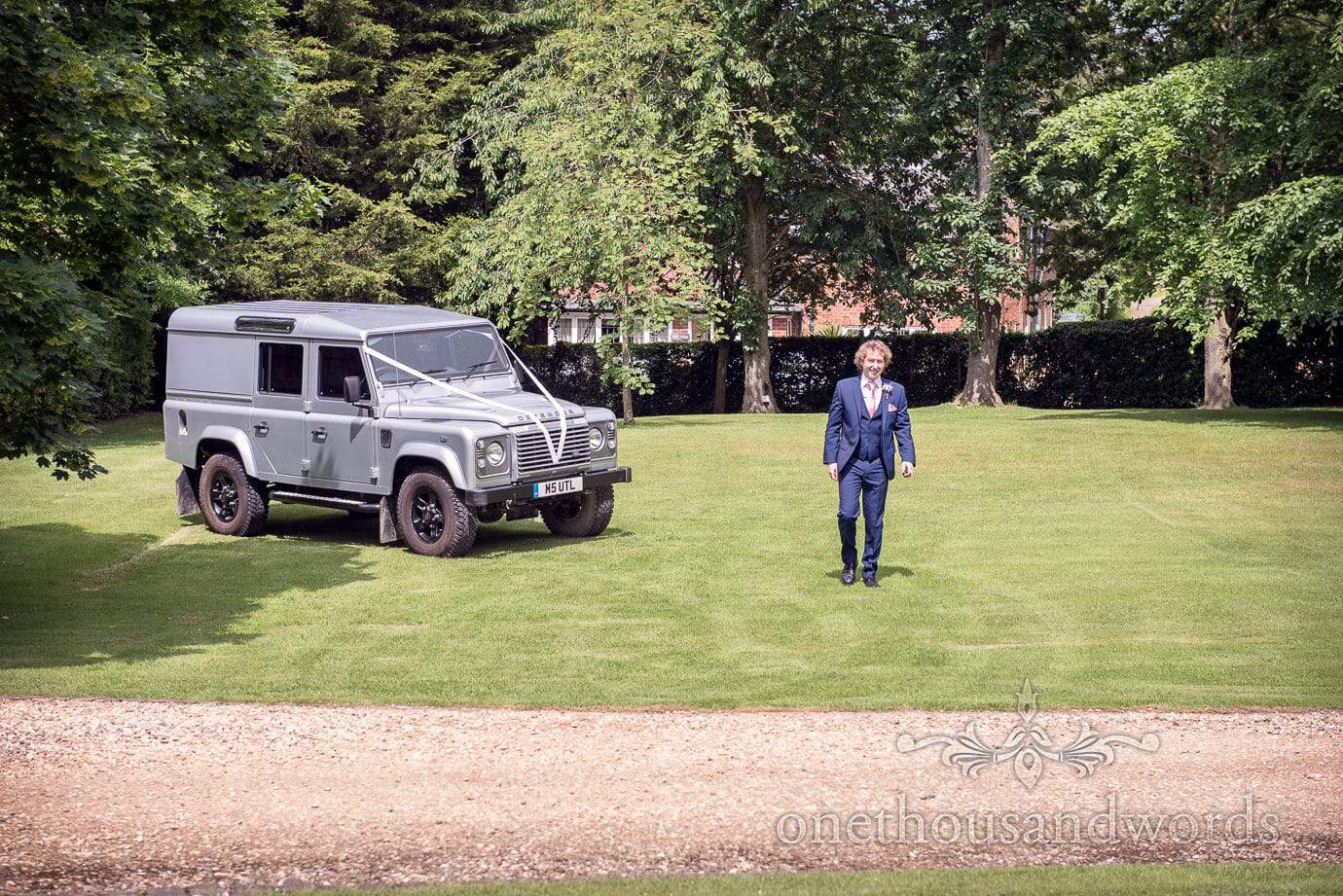 Groomsman in blue wedding suit delivers grey wedding land rover to country wedding