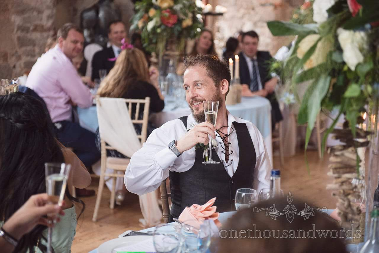 Groomsman in Jacobian shirt and waistcoat toasts wedding speeches at Lulworth Castle