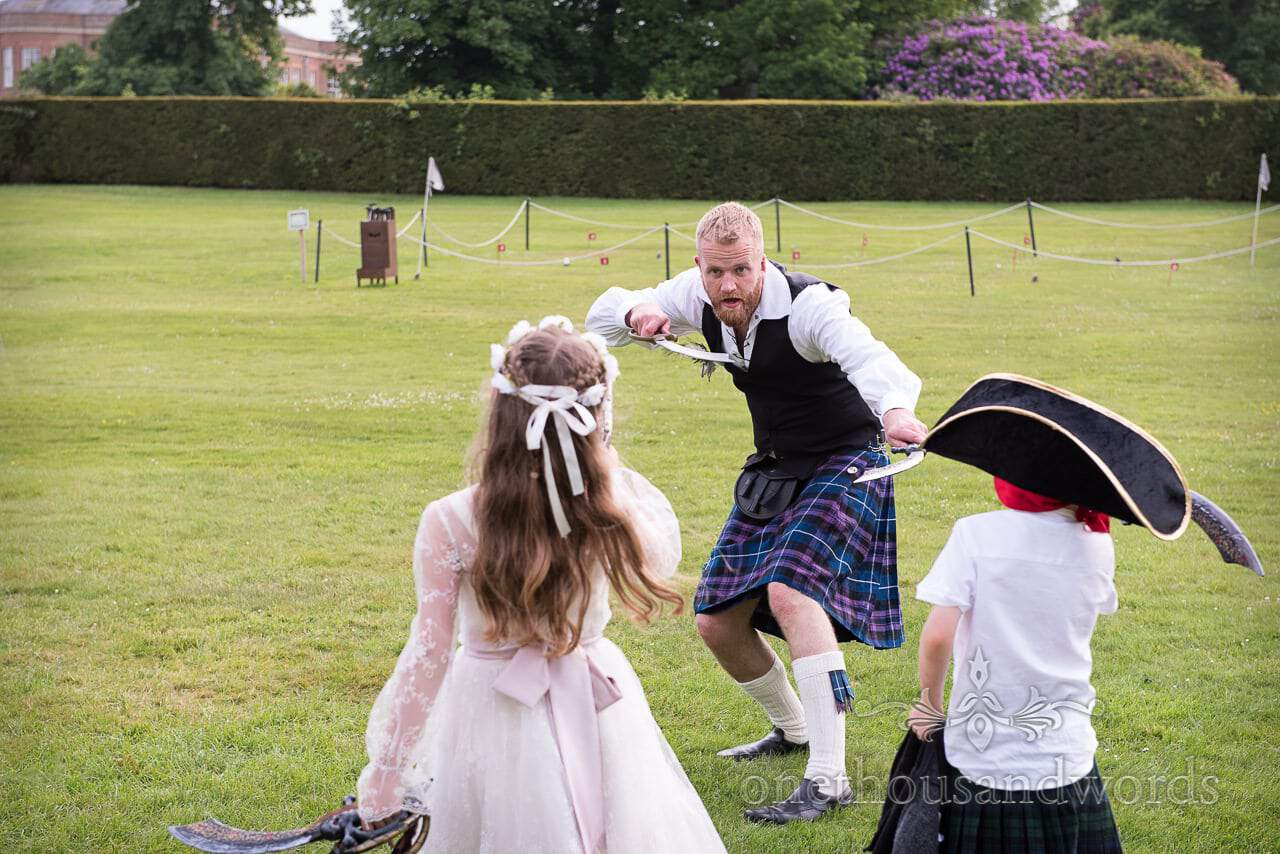 Groomsman in kilt sword fights children at outdoor pirate themed wedding