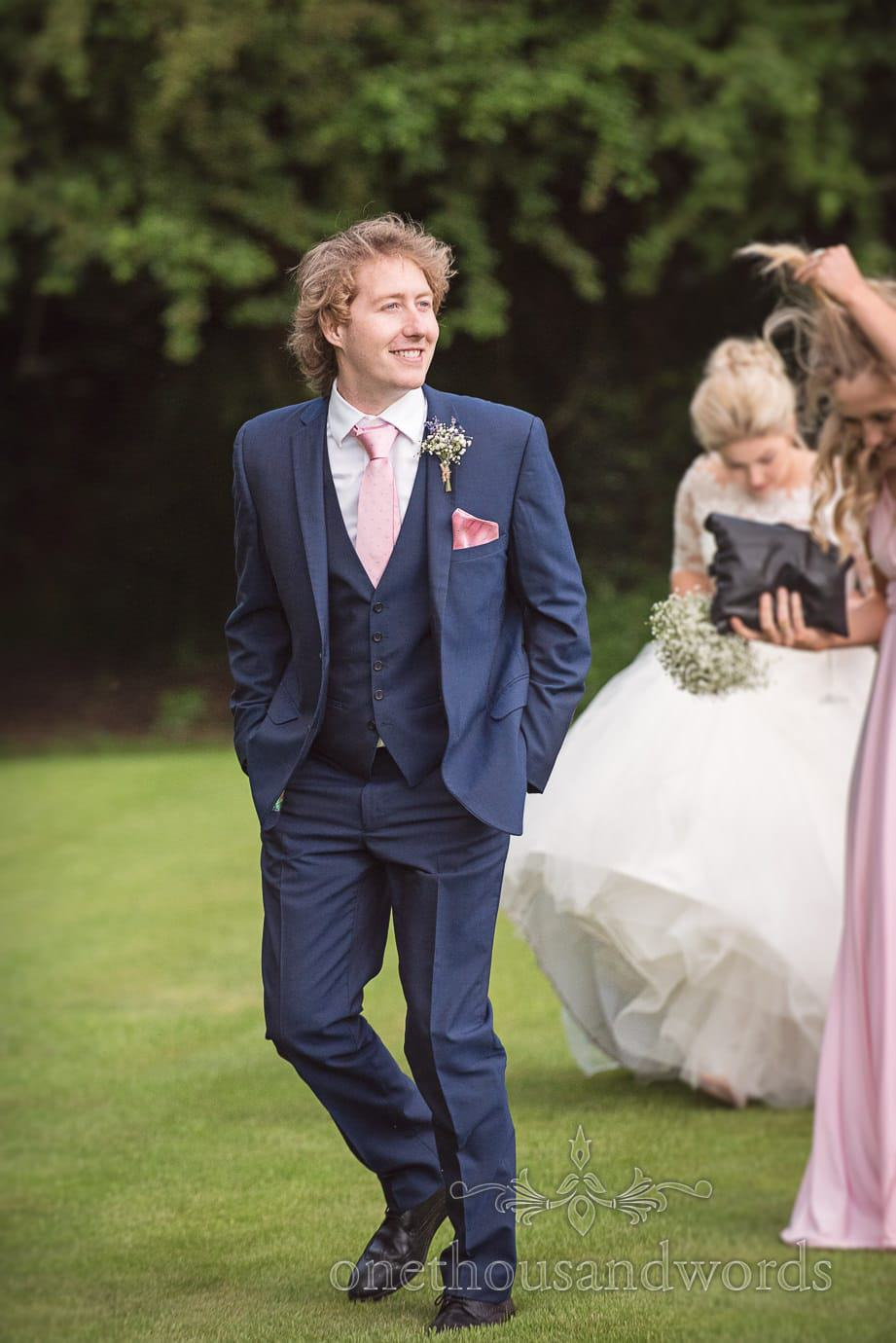 Groomsman in three piece blue wedding suit with pink tie and handkerchief at country wedding