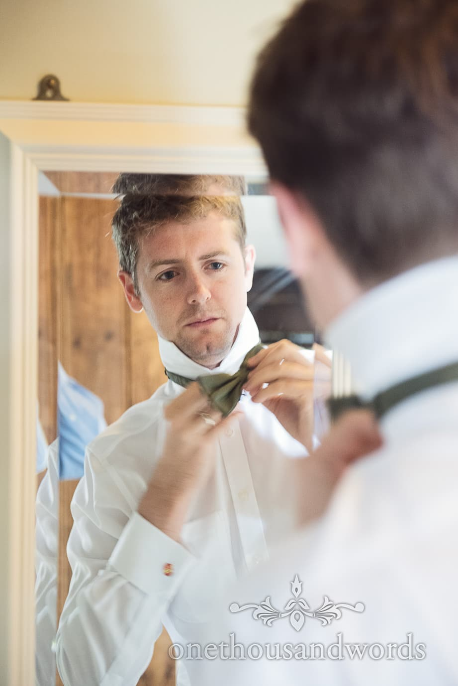 Groomsman prepares with bow tie in mirror on wedding morning in Dorset