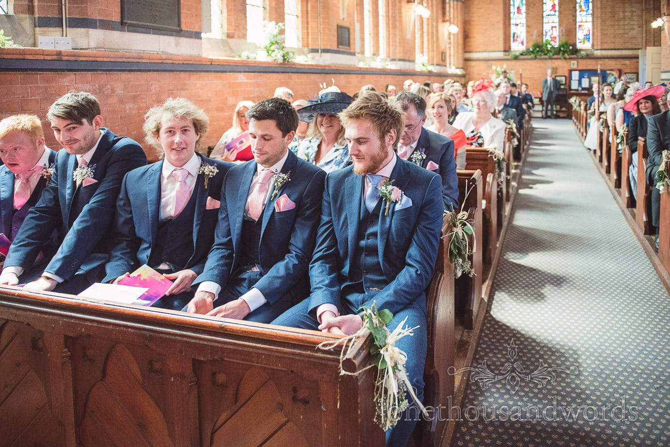 Groomsmen in blue shits and pink ties at church wedding in Leicestershire