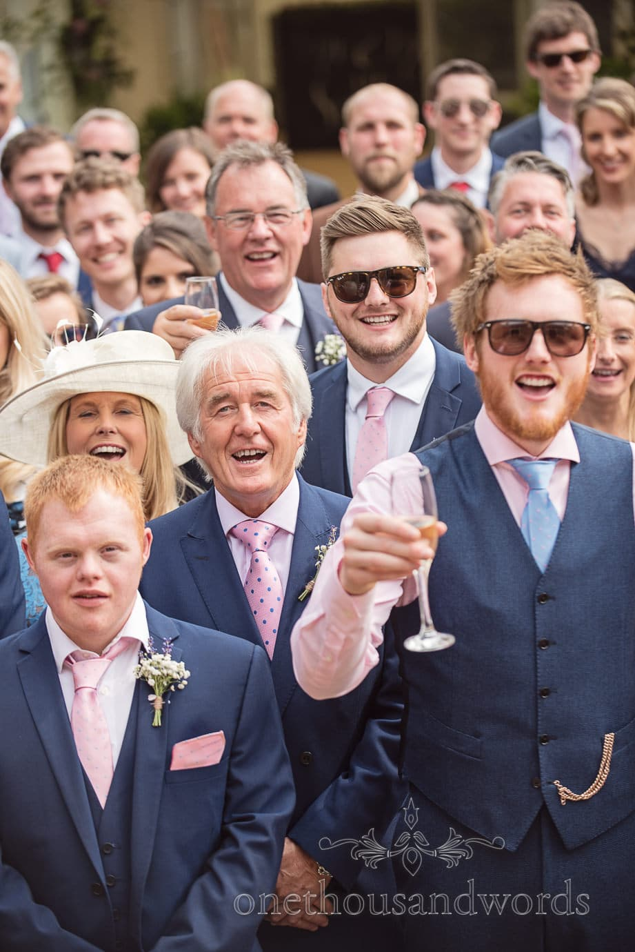 Groomsmen in blue suits and pink ties smile of group wedding photographs