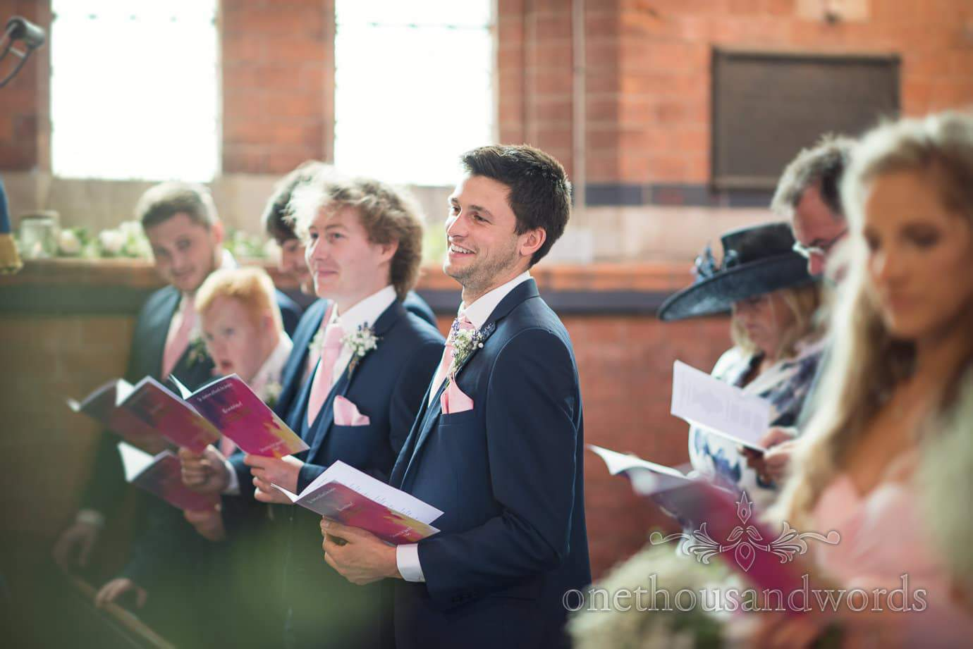 Groomsmen reading from pink multicolour order of service at church wedding