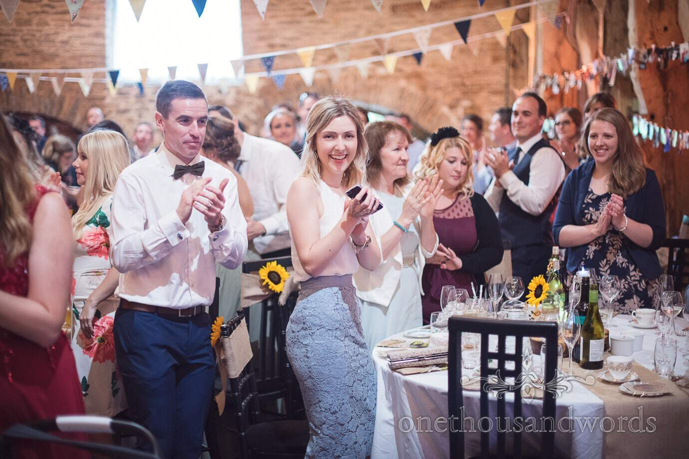 Guests stand and applaud as newly-weds enter rustic barn wedding venue in Dorset