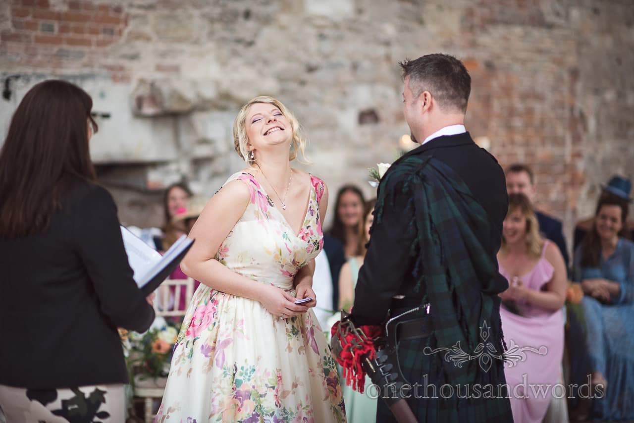 Happy bride in floral wedding dress at Lulworth Castle civil wedding ceremony