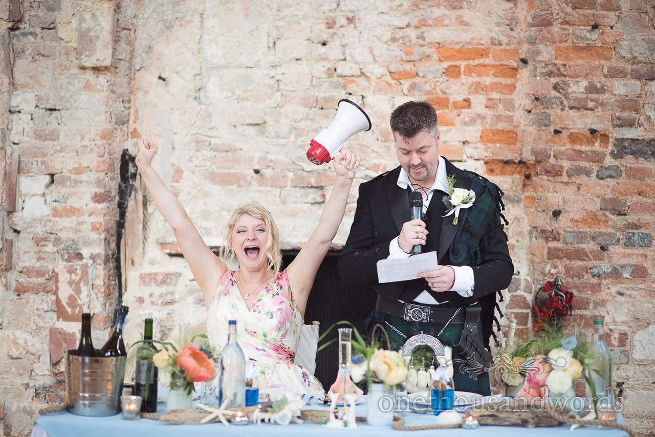Happy bride with megaphone during kilted groom's wedding speech at Lulworth Castle