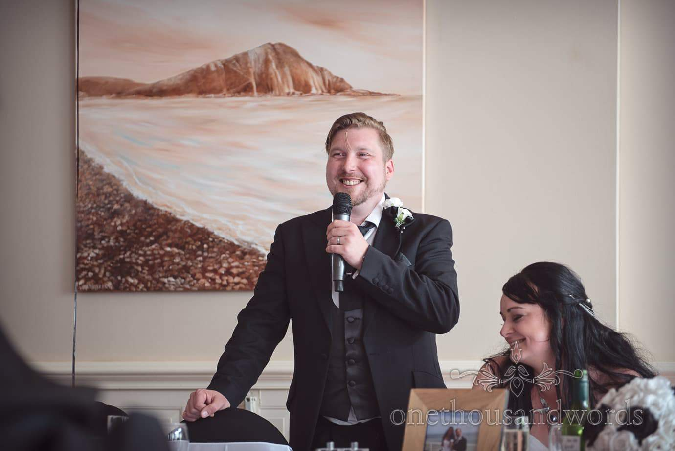 Happy groom makes wedding speech at black and white themed wedding