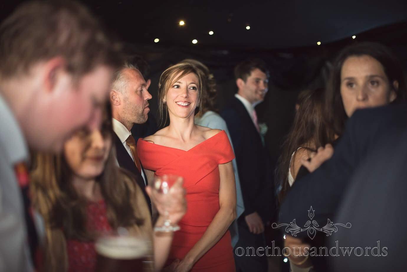 Happy wedding guest in red dress dances in black walled wedding marquee