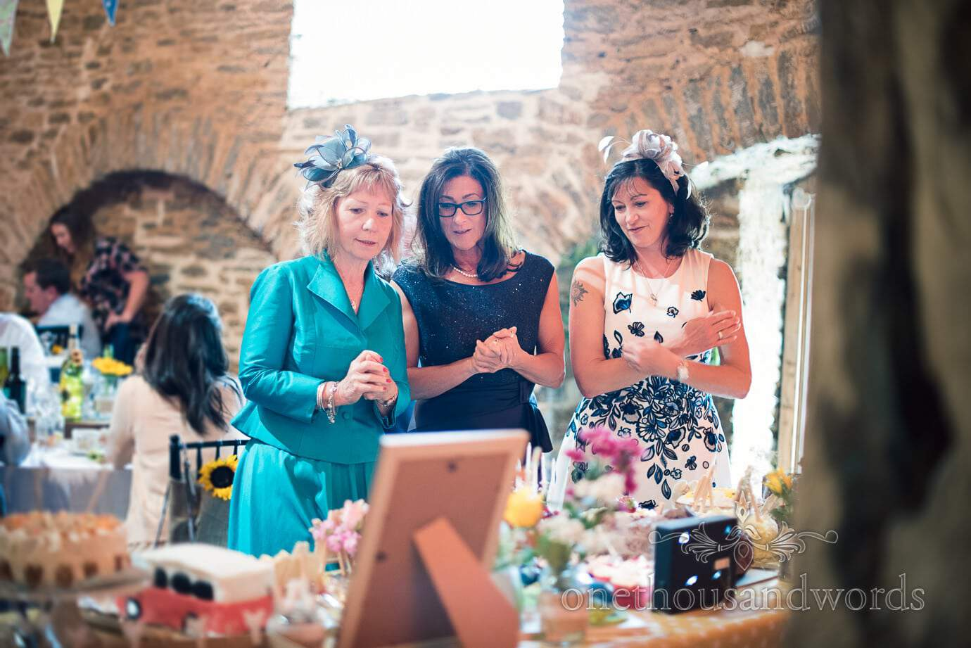 Judges deliberate at cake competition at rustic barn wedding