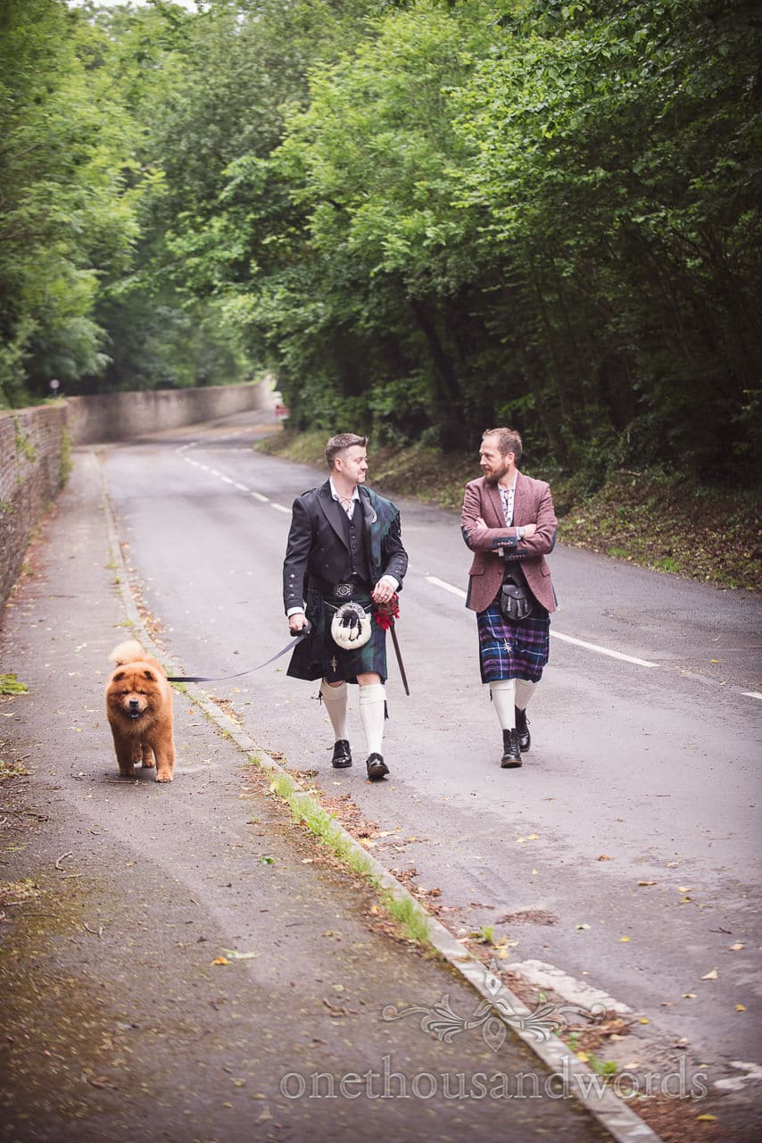 Kilt wearing groom and groomsman with dog walking down road