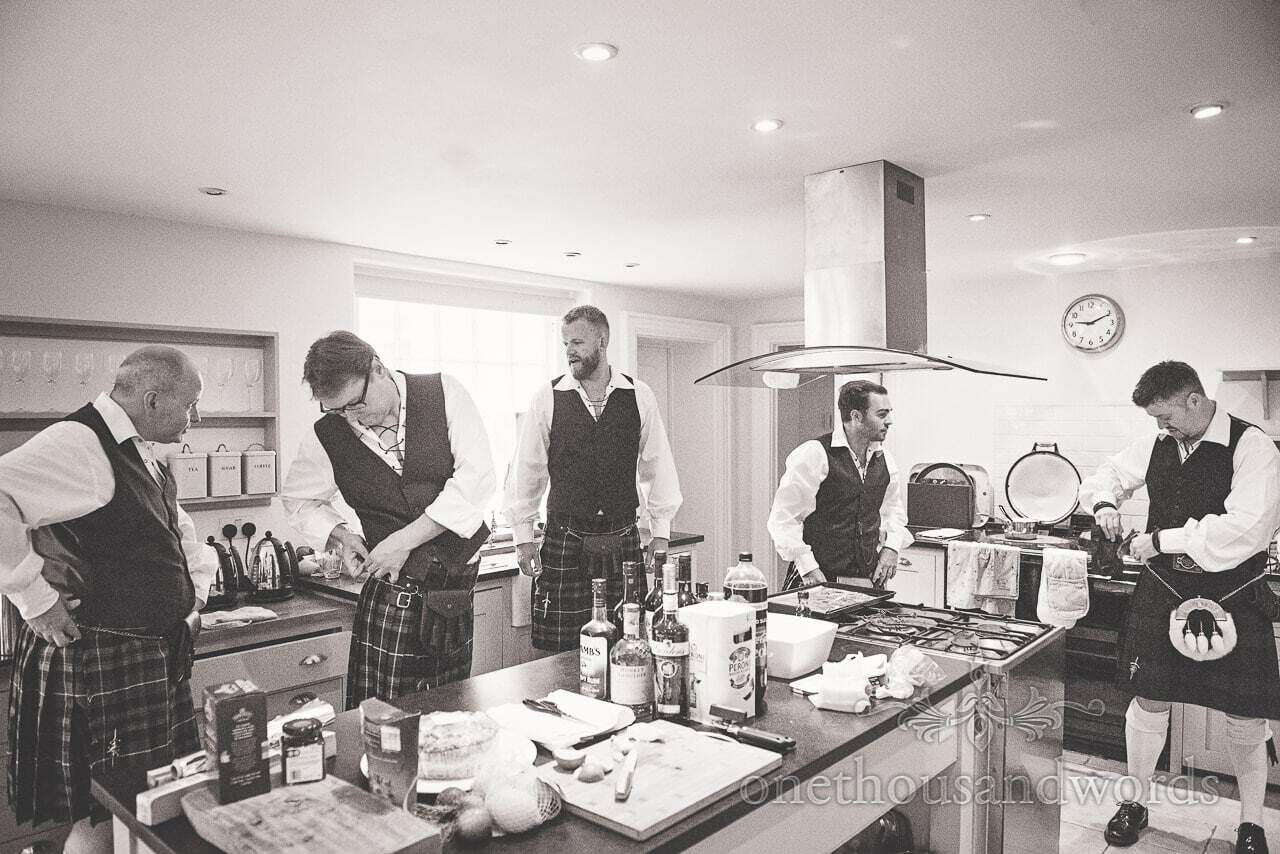 Kilt wearing groom and groomsmen prepare before lulworth castle wedding