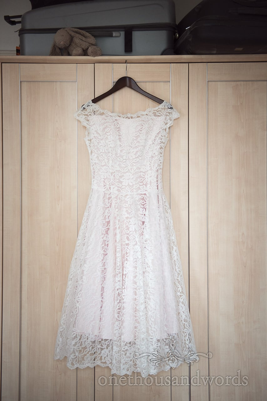 Lace detailed 1950s style wedding dress handing on wardrobe with soft bunny rabbit