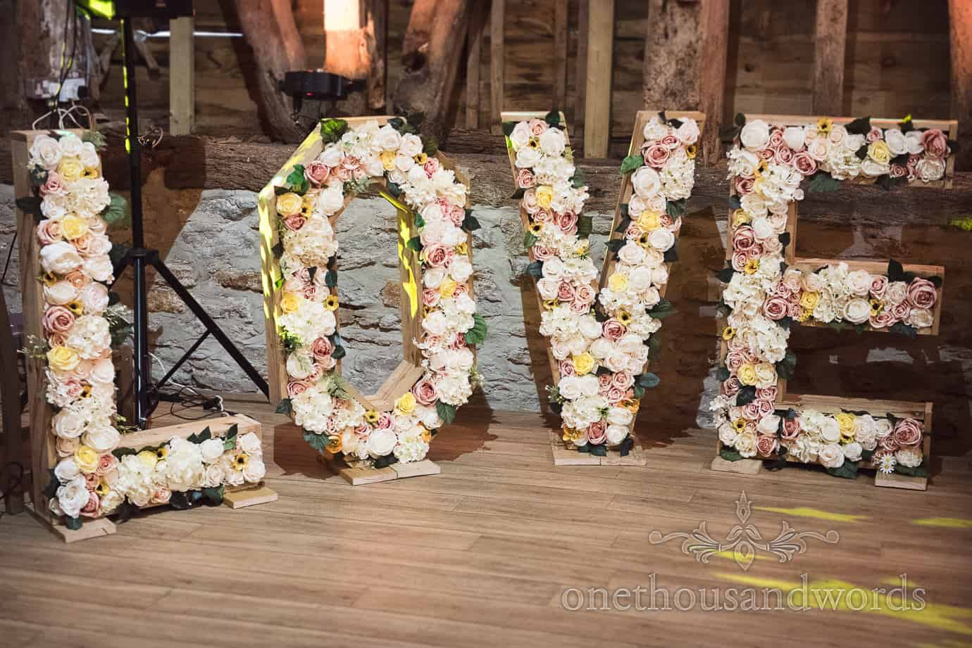 Large Wood and flower LOVE letters at rustic wedding at Stockbridge Farm Barn