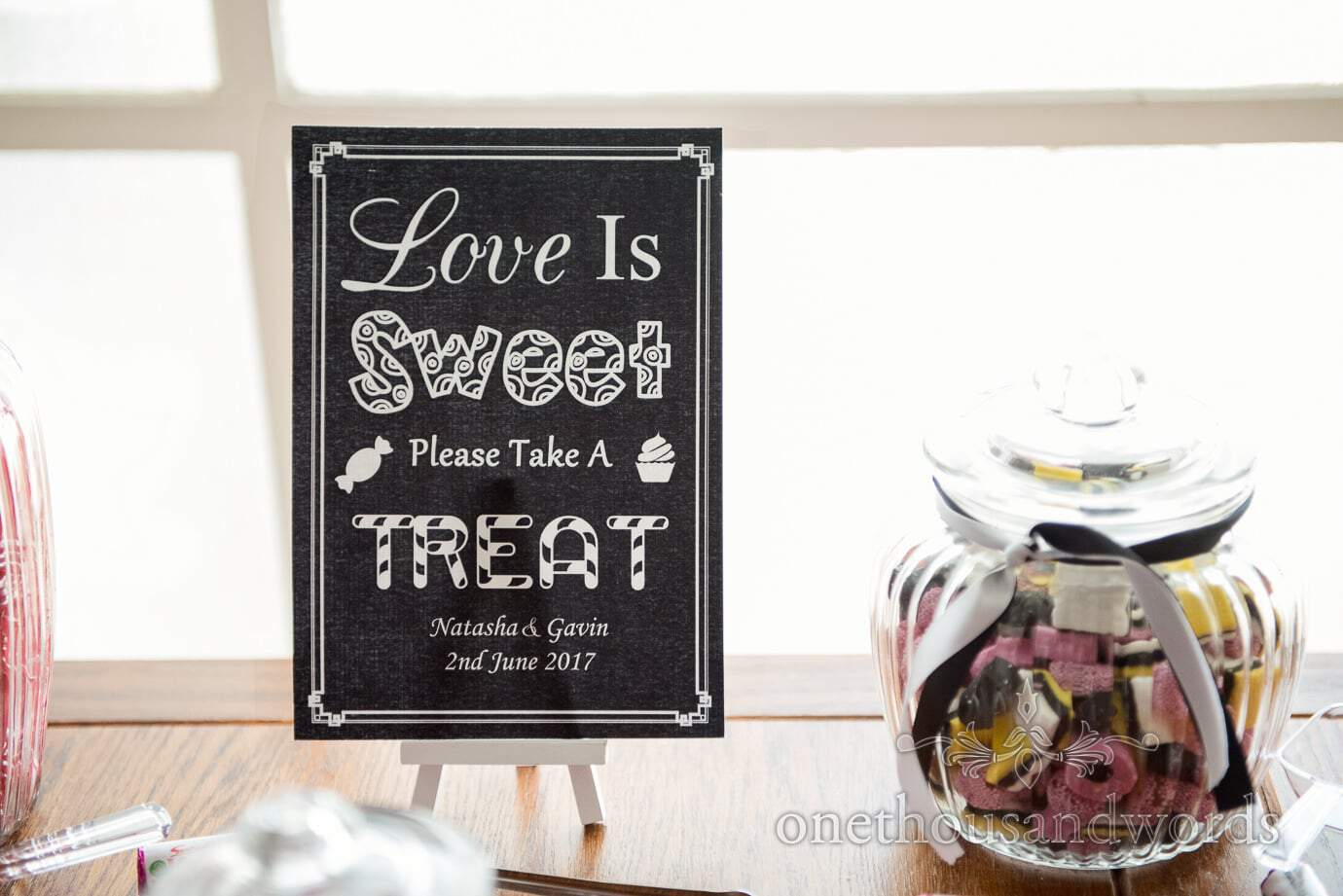 Love is sweet take a treat black and white sign on mini easel with wedding sweet jar