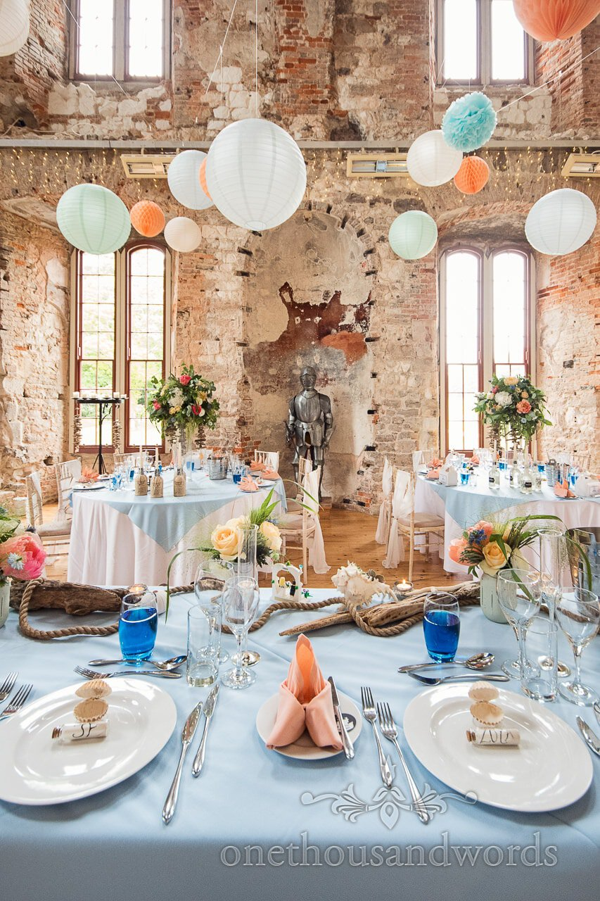 Lulworth Castle wedding breakfast room with oranges and blues and Chinese lanterns and suit of armour