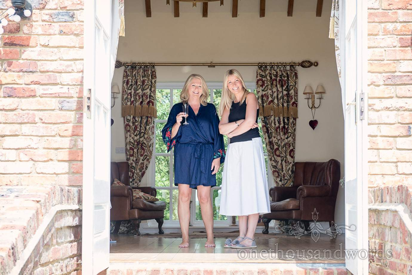 Mother of the bride and friend look out of doorway during wedding morning preparations