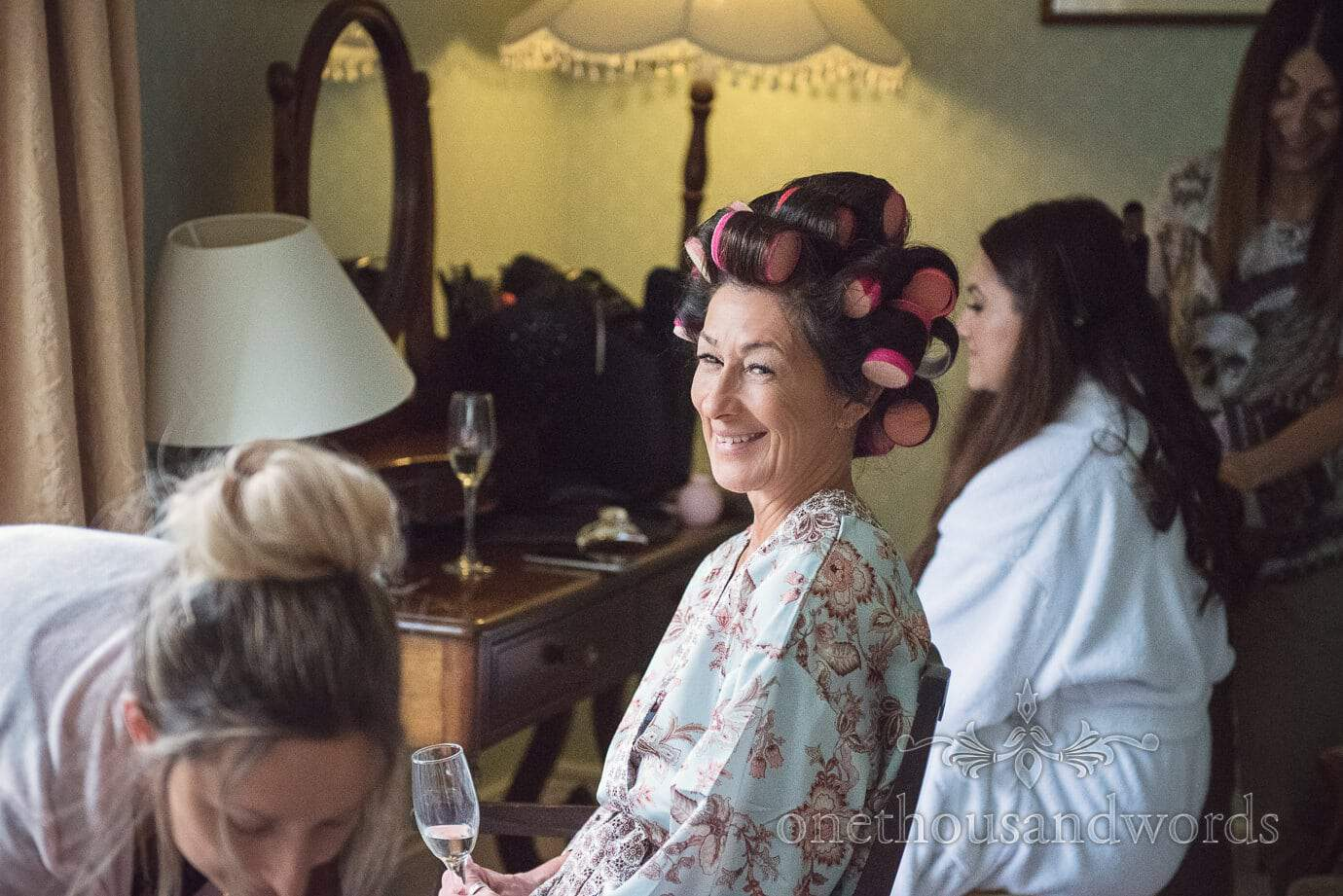 Mother of the bride in hair curlers whilst having wedding hair styled on wedding morning