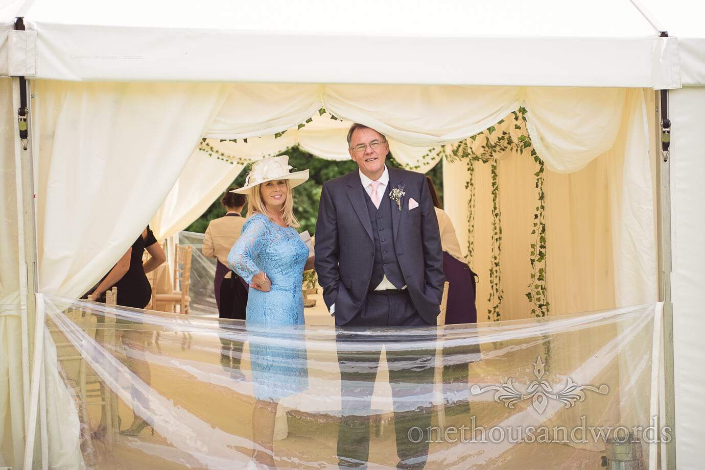 Mother of the bride in sky blue and father of the groom look out of wedding marquee