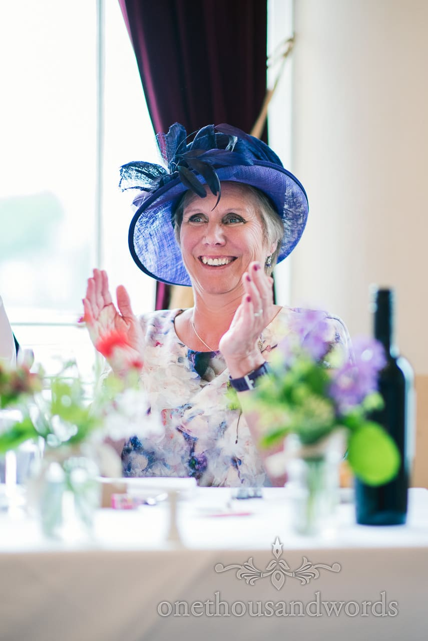 Mother of the bride laughs and claps in blue hatinator at Greenwich wedding