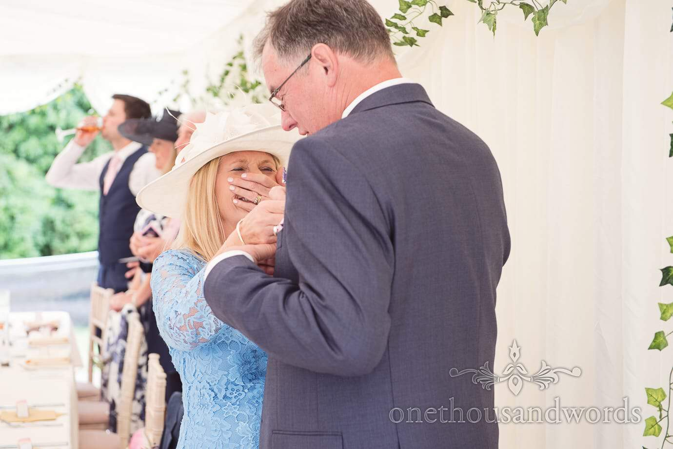 Mother of the bride laughs as she adjusts father of the groom's buttonhole