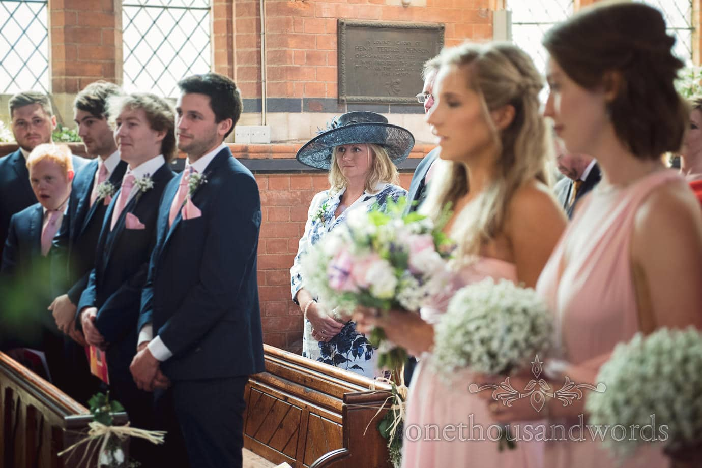 Mother of the groom wears blue wedding hat at church wedding ceremony