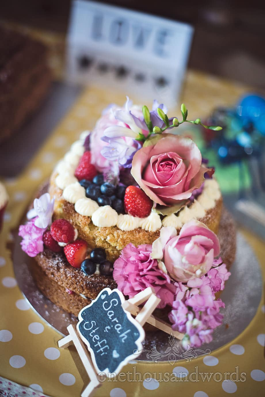 Naked cake decorated with fruit and flowers at rustic wedding