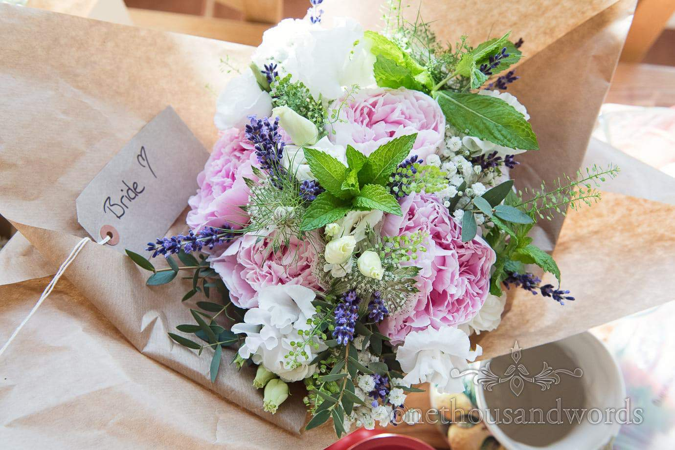 Natural pink, blue and white wedding flowers bouquet with mint at country wedding