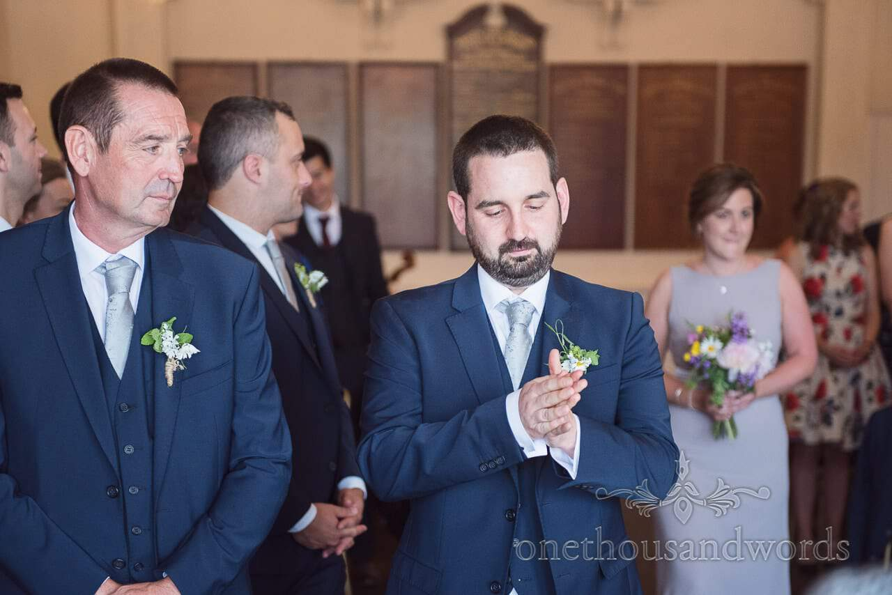 Nervous groom waits for bride with bridesmaid procession in background at Greenwich wedding