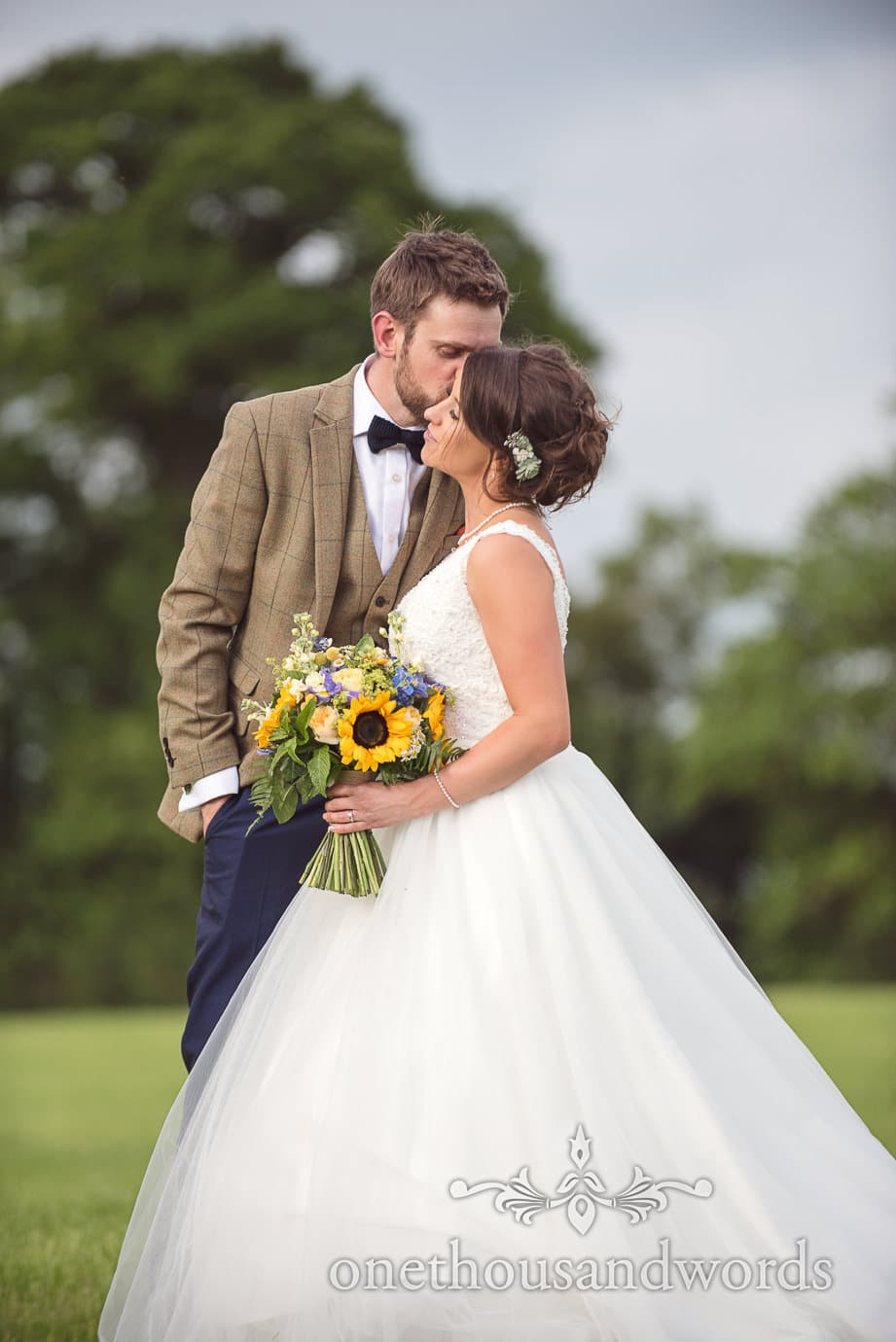 Newly-weds share a kiss in a field at rustic wedding in Dorset countryside
