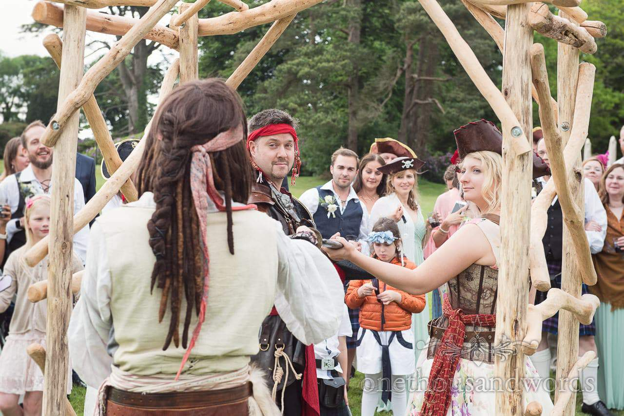 Outdoor pirate themed wedding ceremony under driftwood archway