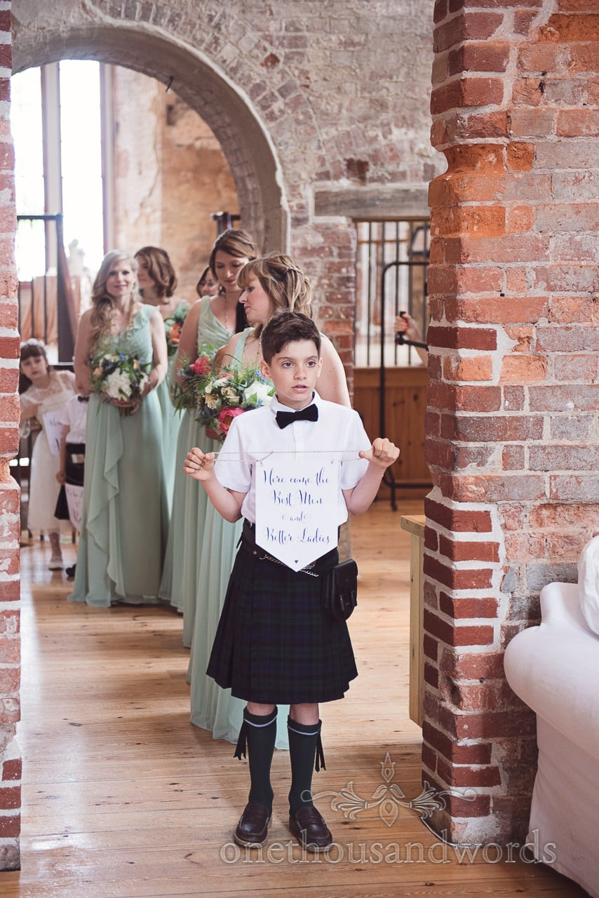 Page boy with message leads the bridesmaids into the ceremony at Lulworth castle wedding
