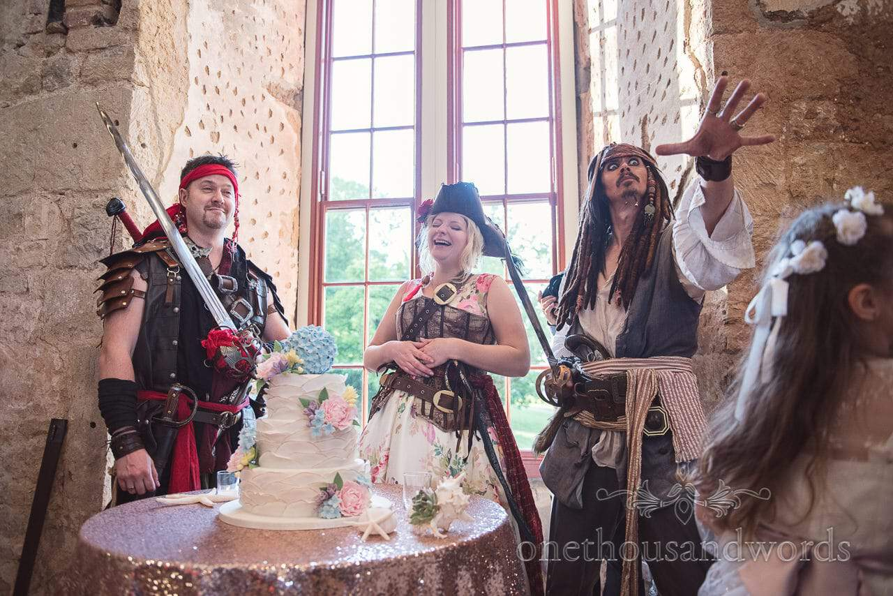 Pirate bride and groom cut the cake with Jack Sparrow lookalike at Pirate wedding