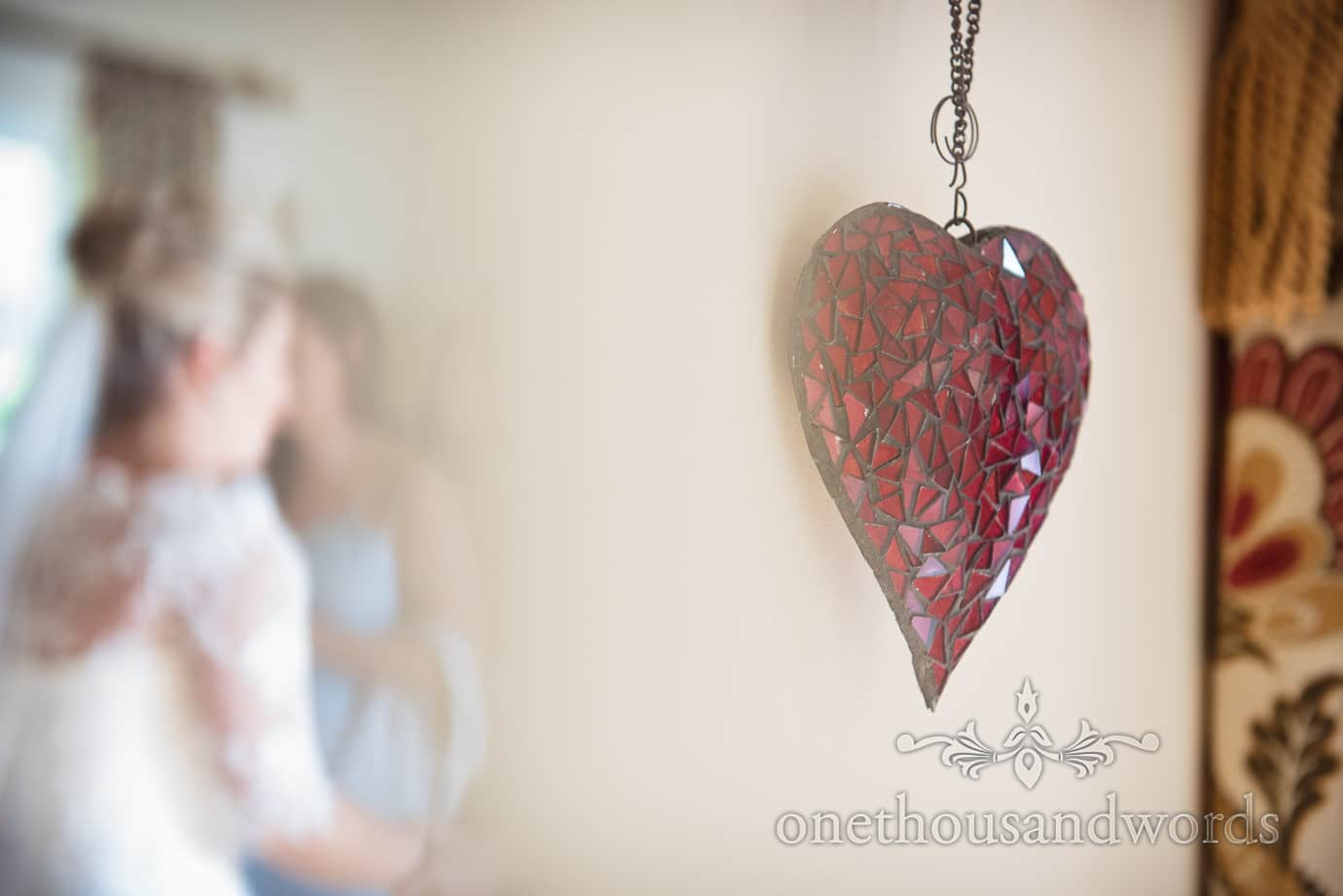 Red glass love heart wedding decoration with bride in background